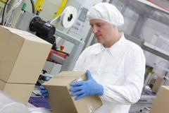 Handarbeider bij productielijn die dozen behandelen royalty-vrije stock foto