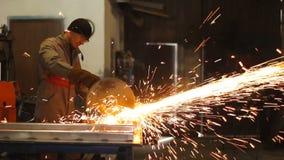 Handarbeider in het cirkelblad van de staalfabriek op stuk van metaal Dolly schot stock videobeelden