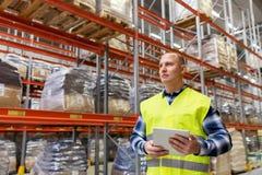 Handarbeider met tabletpc bij pakhuis stock fotografie