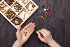 Handarbeit zu Hause, das Mädchen stellt Schmuckhände auf dem Tisch her lizenzfreie stockfotos