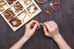 Handarbeit zu Hause, das Mädchen stellt Schmuckhände auf dem Tisch her stockfotografie