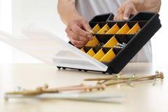 Handarbeitskraft wählen eine Schraube vom Kasten, Abschluss oben Lizenzfreie Stockfotos