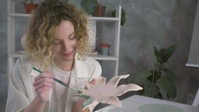 Handarbeittöpferware, lächelnde Handwerkerberufsfrau hält Tonware und setzt bunte Färbung mit Bürste in Kunst stock video