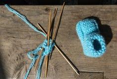 Handarbete av sockor av blå ull arkivfoto