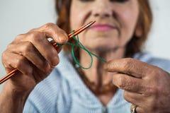handarbete Elegant äldre kvinnainnehavvisare och ull i hand och att göra att sticka under hennes fritid Seniour dam på arkivfoto