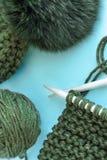 Handarbete, handarbete, garn, halsduk och hatt med en pompongräsplan på en blå bakgrund, utrymme för text som är fiatlay royaltyfria bilder
