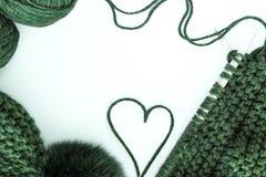 Handarbete, handarbete, garn, halsduk och hatt med en pompongräsplan på en vit bakgrund, utrymme för text som är flatlay arkivfoton