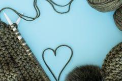 Handarbete handarbete, hjärta av garn-, halsduk- och hattgräsplan på en blå bakgrund, utrymme för text, fritt utrymme fotografering för bildbyråer