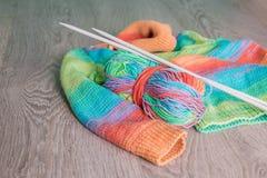 handarbete Stucken tröja Flerfärgat garnnystan med visare nära de handgjorda produkterna på grå träbakgrund royaltyfri bild