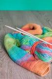 handarbete Stucken tröja Flerfärgat garnnystan med visare nära de handgjorda produkterna på grå träbakgrund royaltyfria bilder