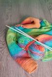 handarbete Stucken tröja Flerfärgat garnnystan med visare nära de handgjorda produkterna på grå träbakgrund royaltyfri fotografi