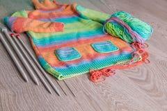 handarbete Stucken tröja Flerfärgat garnnystan med visare nära de handgjorda produkterna på grå träbakgrund royaltyfri foto