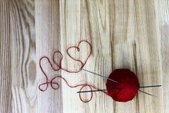 Handarbetebegrepp Ull klumpa ihop sig och den hjärta formade tråden på träbakgrund Royaltyfria Bilder