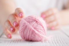 Handarbetegarn vred i clews på träbakgrund, ljus - rosa färg Royaltyfria Bilder