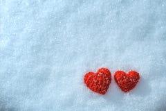 Handarbetehjärtan på en snöig bakgrund Hälsningkort för dal Arkivbild