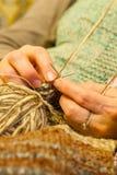 Handarbeteplats av kvinnahänder som virkar en ullväst och en brun boll av ull royaltyfri bild