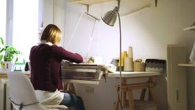 Handarbetetextil för ung kvinna på att väva maskinsammanträde på tabellen i seminarium lager videofilmer