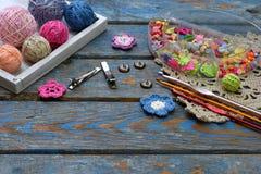 Handarbetetillbehör för att skapa virkade smycken Pärlor dragar, krokar, knappar på träbakgrund Sticka virkning, emb royaltyfri fotografi