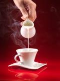 Handauslaufende Milch in der Kaffeetasse Stockfotos