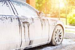 Handautowasserette Het voertuig van de wasluxe met wit schuimend detergens Automobiele schoonmakende zelfbediening stock fotografie