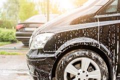 Handautowasserette Het voertuig van de wasluxe met wit schuimend detergens Automobiele schoonmakende zelfbediening stock foto's