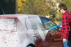 Handautowasserette met onder druk gezet buiten water in autowasserette E Schoonmakende Auto die Hoge drukwater gebruiken royalty-vrije stock afbeeldingen
