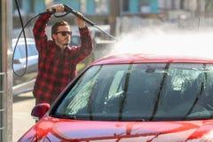 Handautowasserette met onder druk gezet buiten water in autowasserette E Schoonmakende Auto die Hoge drukwater gebruiken stock afbeelding