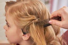 Handbürstendes Haar des Kindes Stockbilder