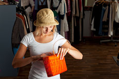 Handbag. Young woman searching her handbag in a boutique stock photography
