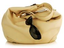 Handbag and antisun glasses. Female light handbag and antisun glasses on white Royalty Free Stock Photos