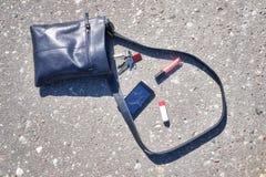 Handbag, broken phone, keys and lipstick on asphalt street. royalty free stock image
