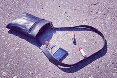 Handbag, broken phone, keys and lipstick on asphalt street. stock images