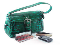 Handbag with cell phone and makeup. Green designer leather handbag with c grey cell phone, mascara, lip gloss and eye shadows - isolated on white Stock Images