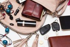 Handbag. The contents of the female handbag - wallet, keys, phone, lipstick, perfume royalty free stock photos