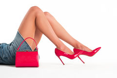 Handbag and female legs. Red purse and heels. How to dress up sexy. Expensive footwear from designer royalty free stock photography