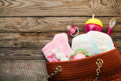 Handbag with items to care for child. Mothers handbag with items to care for child stock photography
