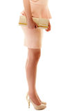 Handbag and legs of girl in pink dress and high heels. Female elegance. Shiny handbag and sexy legs of girl in light pink dress or skirt and high heels isolated Stock Photos