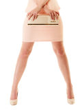 Handbag and legs of girl in pink dress and high heels. Female elegance. Shiny handbag and sexy legs of girl in light pink dress or skirt and high heels isolated Stock Image