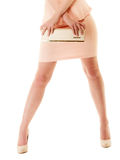 Handbag and legs of girl in pink dress and high heels. Female elegance. Shiny handbag and sexy legs of girl in light pink dress or skirt and high heels isolated Stock Images