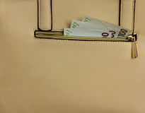 Handbag with money. Beige handbag with money in pocket, detail view Royalty Free Stock Photo