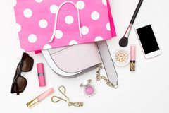 Handbag in a pink shopping bag and female accessories on a white Stock Photography