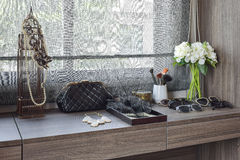 Handbag,sunglasses,jewelry and makeup brushes on dressing table Royalty Free Stock Image