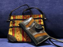 Handbag and wallet. An handbag with its wallet,both made of leather and colored on a blu background Stock Photography