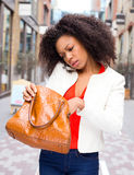 Handbag. Young woman on the phone loonking in her handbag stock photos