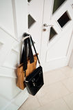 Handbags on door handle. Two leather handbags hanging on door handle of white door Stock Images
