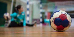 Handball ball on court floor. Blurred female goalkeeper background. Space for text, close up view. Stock Photography