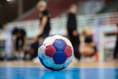 Handball ball on court` s floor. Blurred referees, coaches and athletes and field background. Royalty Free Stock Photography