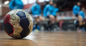 Handball ball on floor. Blurred exercising team background. Space for text. Royalty Free Stock Photos