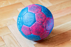 Handball Ball on Wooden a Parquet Floor. Dirty blue and red handball ball on a wooden parquet floor Royalty Free Stock Image