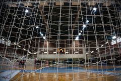 Handball concept. Goal post nets from behind view. Blurred court, athletes and electronic scoreboard background. Handball concept. Close up goal post nets from Stock Images
